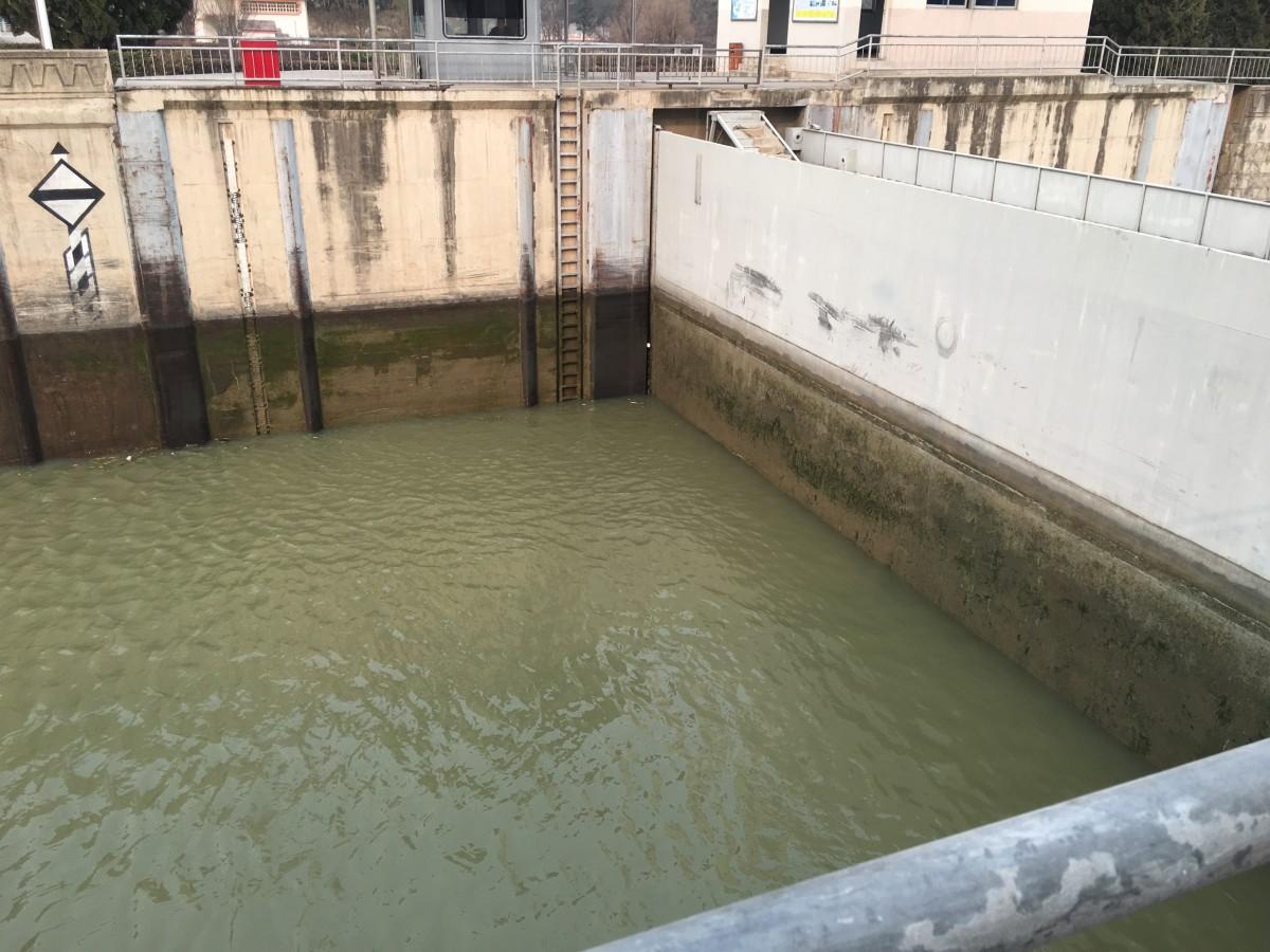 闸门底部的阀门开启,闸室内部开始缓缓泄水,消除闸室内部与下游河段的落差